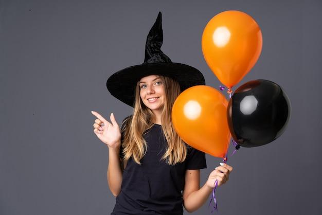 Menina com fantasia de bruxa para festa de halloween e apontando para a lateral