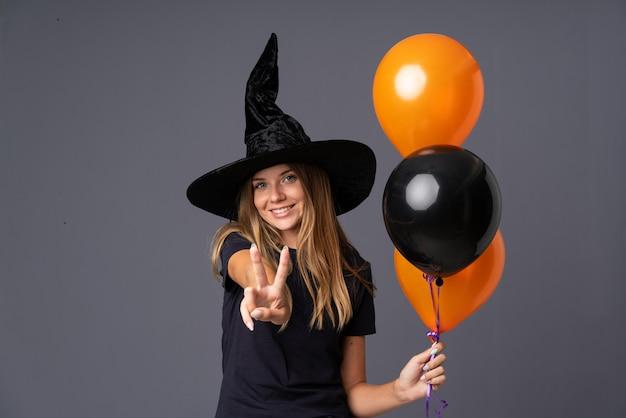 Menina com fantasia de bruxa para festa de halloween e fazendo gesto de vitória