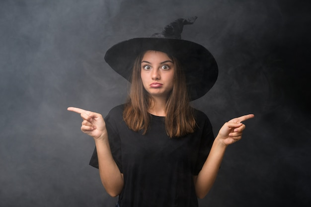 Menina com fantasia de bruxa para festas de halloween ao longo da parede escura isolada, apontando para as laterais com dúvidas