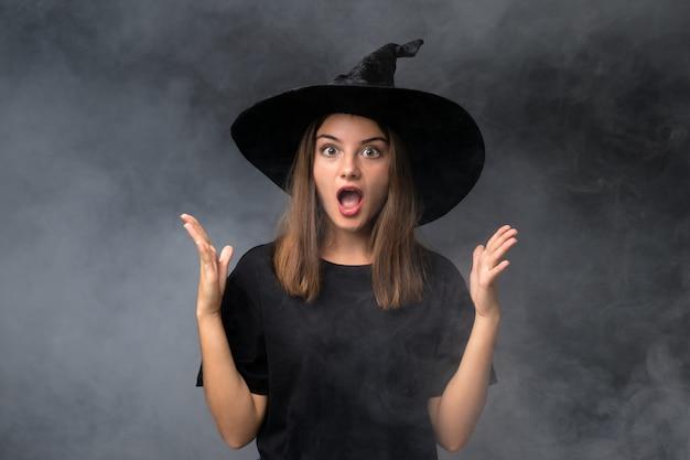 Menina com fantasia de bruxa para festas de halloween ao longo da parede escura isolada com expressão facial de surpresa