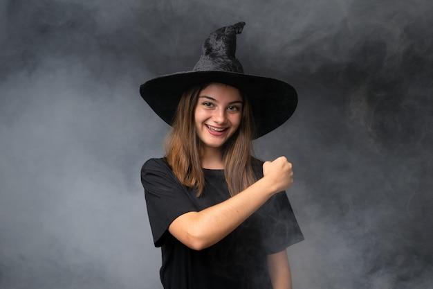 Menina com fantasia de bruxa para festas de halloween ao longo da parede escura isolada, comemorando uma vitória