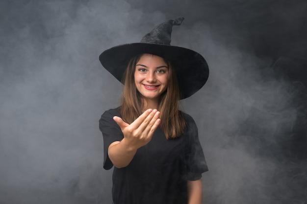 Menina com fantasia de bruxa para festas de halloween ao longo da parede escura isolada, convidando para vir