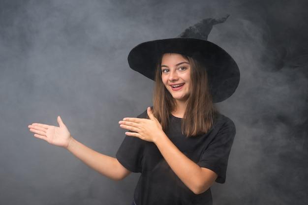 Menina com fantasia de bruxa para festas de halloween ao longo da parede escura isolada, estendendo as mãos para o lado para convidar para vir