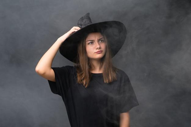 Menina com fantasia de bruxa para festas de halloween ao longo da parede escura isolada, tendo dúvidas e com a expressão do rosto confuso
