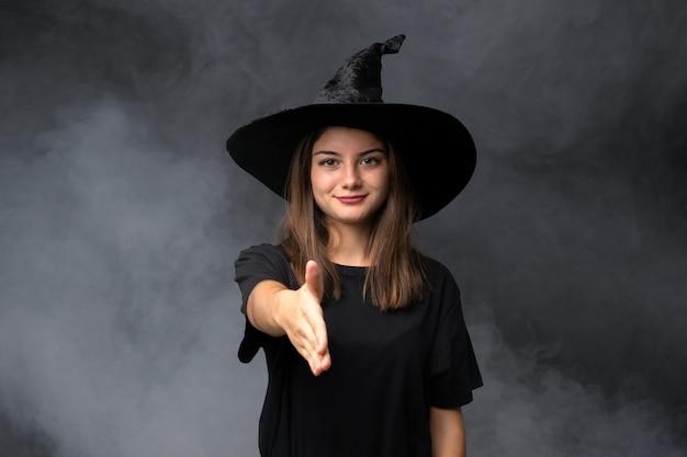 Menina com fantasia de bruxa para festas de halloween sobre aperto de mão isolado parede escura depois de bom negócio
