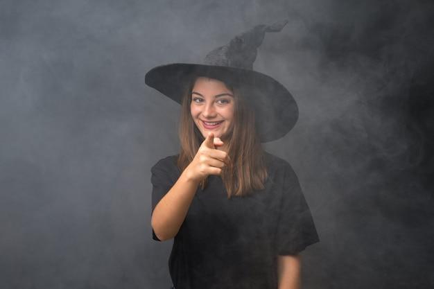 Menina com fantasia de bruxa para festas de halloween sobre dedo de pontos de parede escura isolado para você