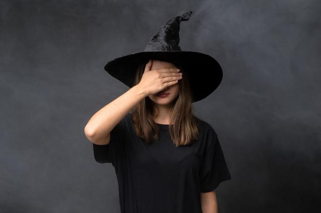 Menina com fantasia de bruxa para festas de halloween sobre parede escura isolada, cobrindo os olhos pelas mãos