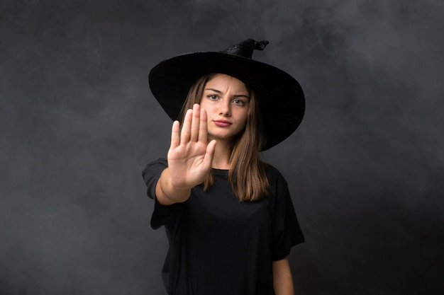 Menina com fantasia de bruxa para festas de halloween sobre parede escura isolada, fazendo o gesto de parada com a mão