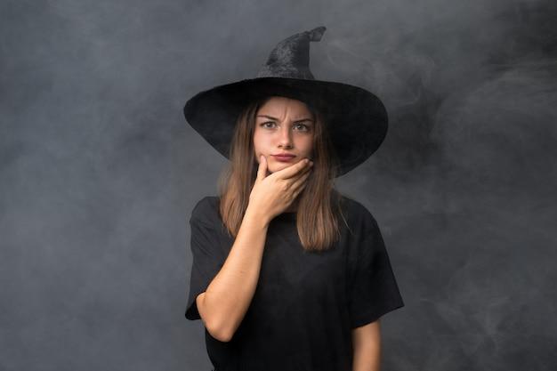 Menina com fantasia de bruxa para festas de halloween sobre parede escura isolada, pensando uma idéia