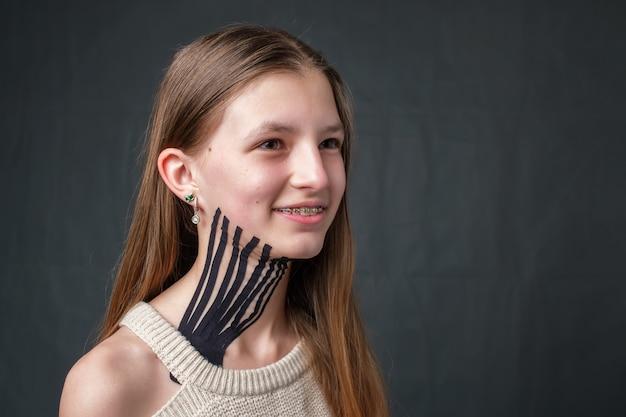 Menina com fita cinesiológica listrada preta colocada no pescoço