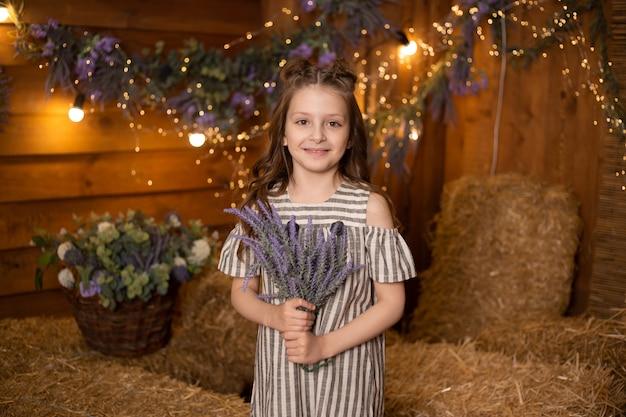 Menina com flores nas mãos na fazenda em pé em feixes de palha no celeiro usando vestido