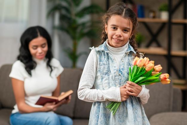 Menina com flores para a mãe dela