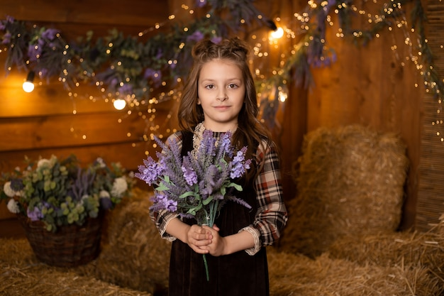 Menina com flores sentado em feixes de palha na fazenda usando vestido retrô
