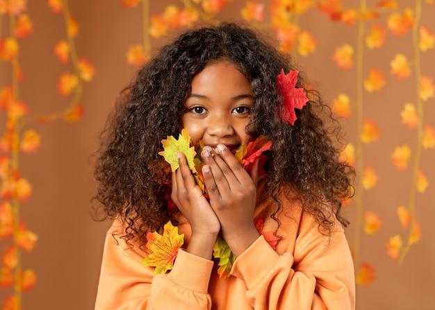 Menina com folhas coloridas tiro médio