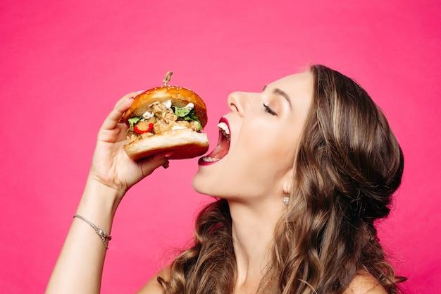 Menina com fome com a boca aberta, comendo hambúrguer grande.