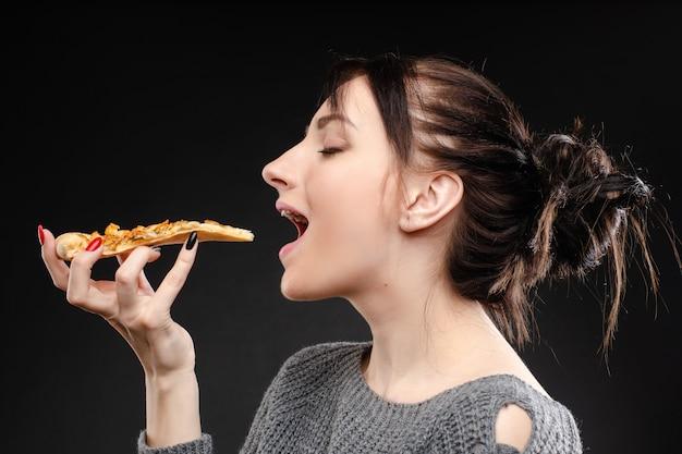 Menina com fome com a boca aberta comendo pizza