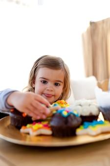 Menina com fome olhando confeitaria em casa