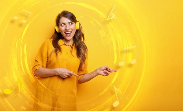 Menina com fone de ouvido amarelo ouve música e dança