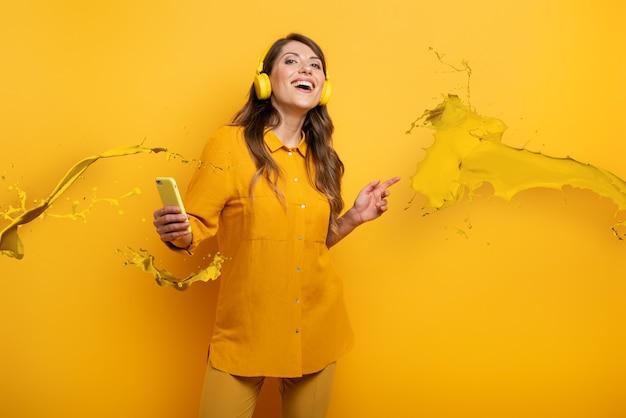 Menina com fone de ouvido amarelo ouve música e danças. expressão emocional e energética