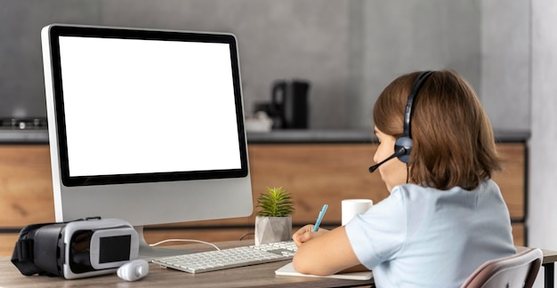Menina com fone de ouvido aprendendo online