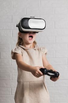 Menina com fone de ouvido de realidade virtual e joystick