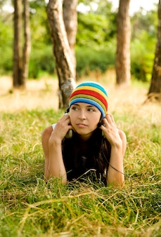 Menina com fone de ouvido no parque.
