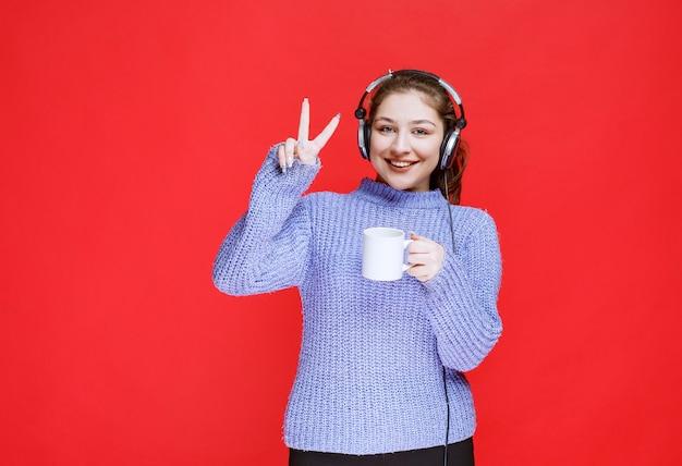 Menina com fones de ouvido, apreciando o sabor do café.