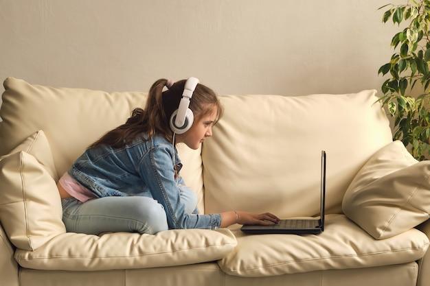 Menina com fones de ouvido assistindo vídeo no sofá em casa