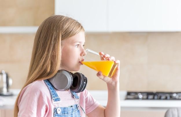 Menina com fones de ouvido, bebendo suco de laranja na cozinha