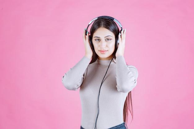 Menina com fones de ouvido checando a música e parece séria