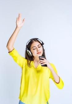 Menina com fones de ouvido, dançando e cantando, segurando um smartphone.