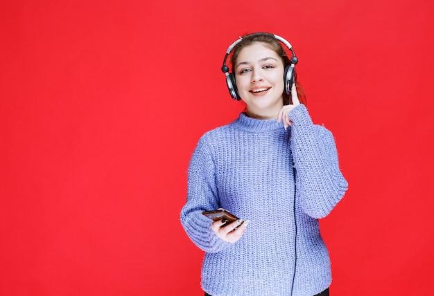 Menina com fones de ouvido, definindo música em seu smartphone e gostando.