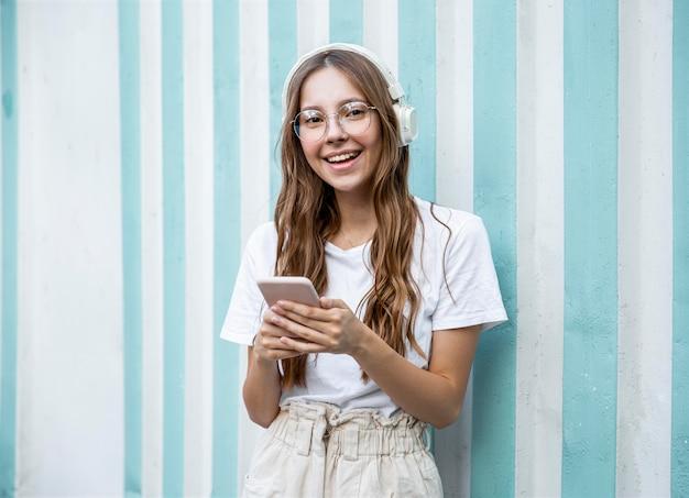 Menina com fones de ouvido e celular