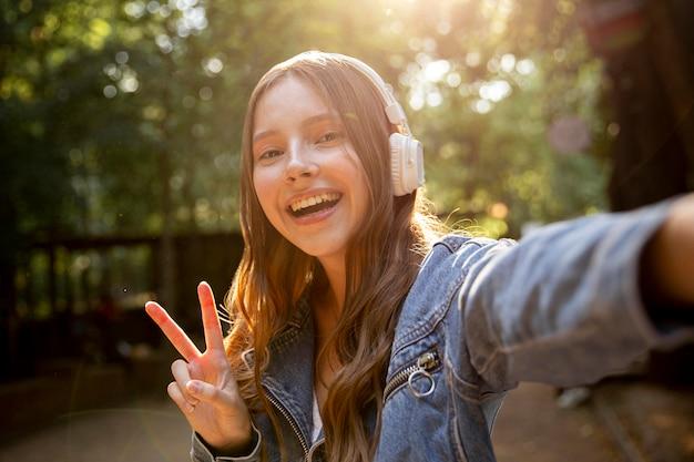 Menina com fones de ouvido e sinal de paz