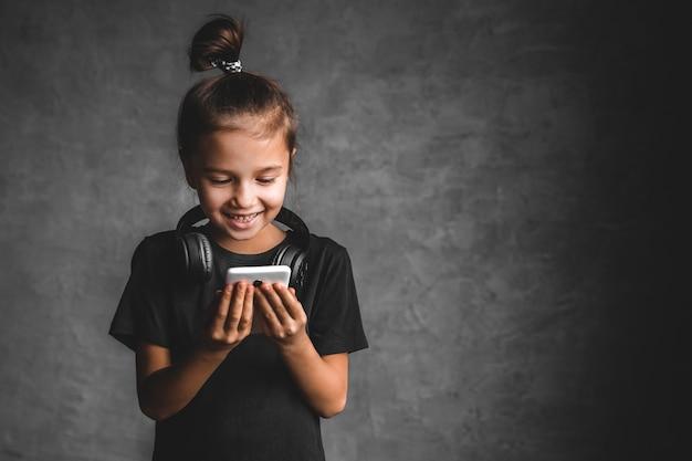 Menina com fones de ouvido e telefone em um fundo cinza