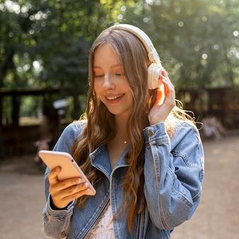 Menina com fones de ouvido, escutando retrato de música