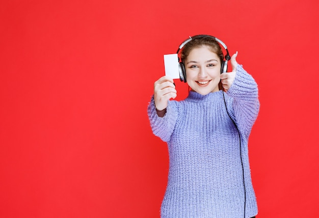 Menina com fones de ouvido, mostrando seu cartão de visita e fazendo sinal de satisfação.
