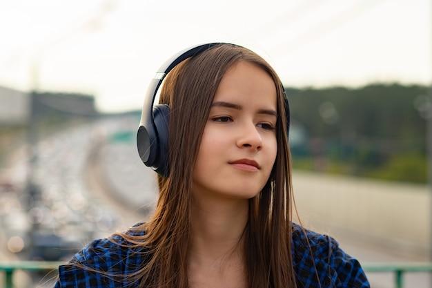 Menina com fones de ouvido na rua ouvindo música no fundo da paisagem da cidade, estrada, carros