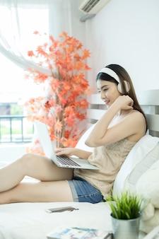Menina com fones de ouvido, ouvindo a música em um laptop na cama em casa