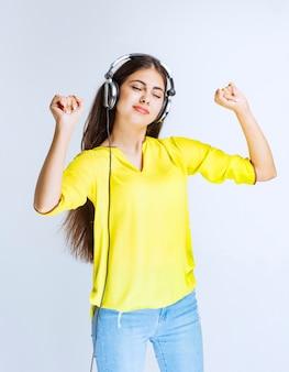 Menina com fones de ouvido, ouvindo música e dançando com paixão.