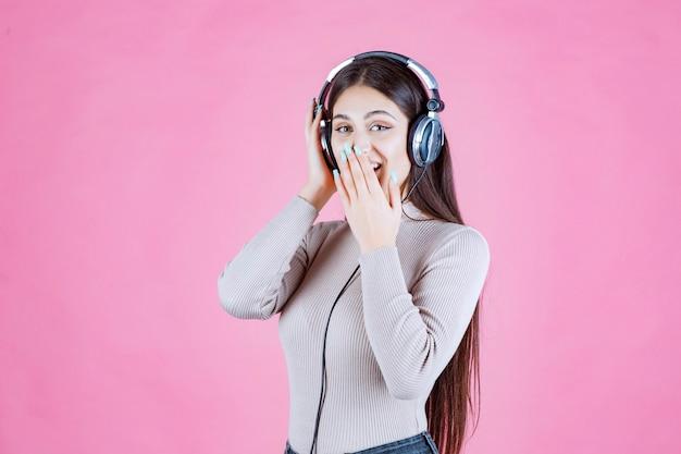 Menina com fones de ouvido, ouvindo música e mostrando que está gostando