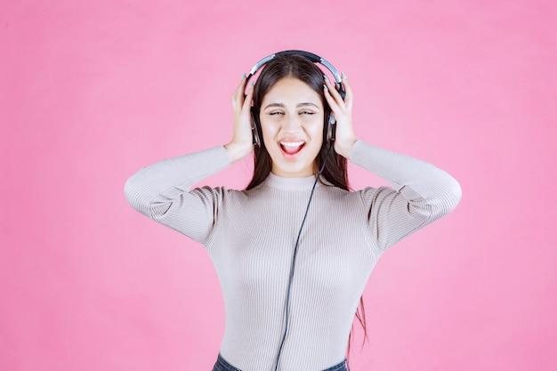 Menina com fones de ouvido ouvindo música e se sentindo feliz