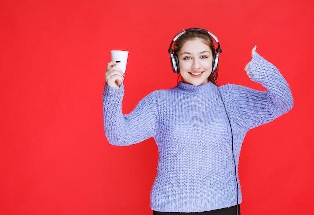 Menina com fones de ouvido, segurando uma xícara de café e mostrando sinal de prazer.