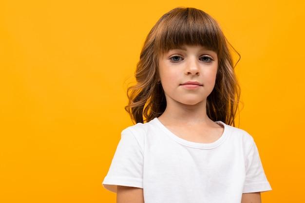 Menina com franja em uma camiseta branca em close-up amarelo