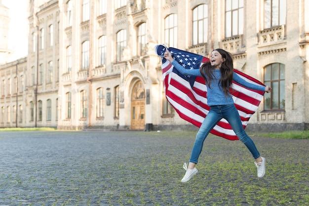 Menina com fundo de arquitetura de bandeira americana ao ar livre, descubra o conceito de eua.