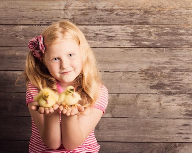Menina com ganso em fundo de madeira