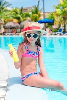 Menina com garrafa de creme de sol sentado na beira da piscina