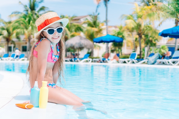 Menina com garrafa de protetor solar na piscina