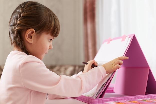 Menina com giz de cera desenhando uma foto sentada à mesa