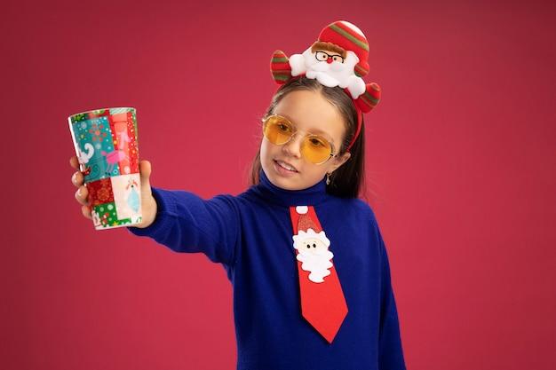 Menina com gola olímpica azul com gravata vermelha e aro de natal engraçado na cabeça segurando um copo de papel colorido olhando para ele feliz e positivo sorrindo em pé sobre a parede rosa